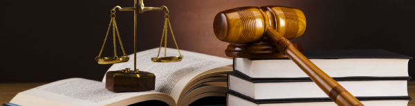 A gavel resting on legal books next to scales